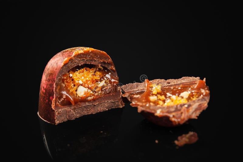 A broken chocolate candy with a red and gold shade on a black background. Inside the filling is made of caramel, nuts and sugar royalty free stock images