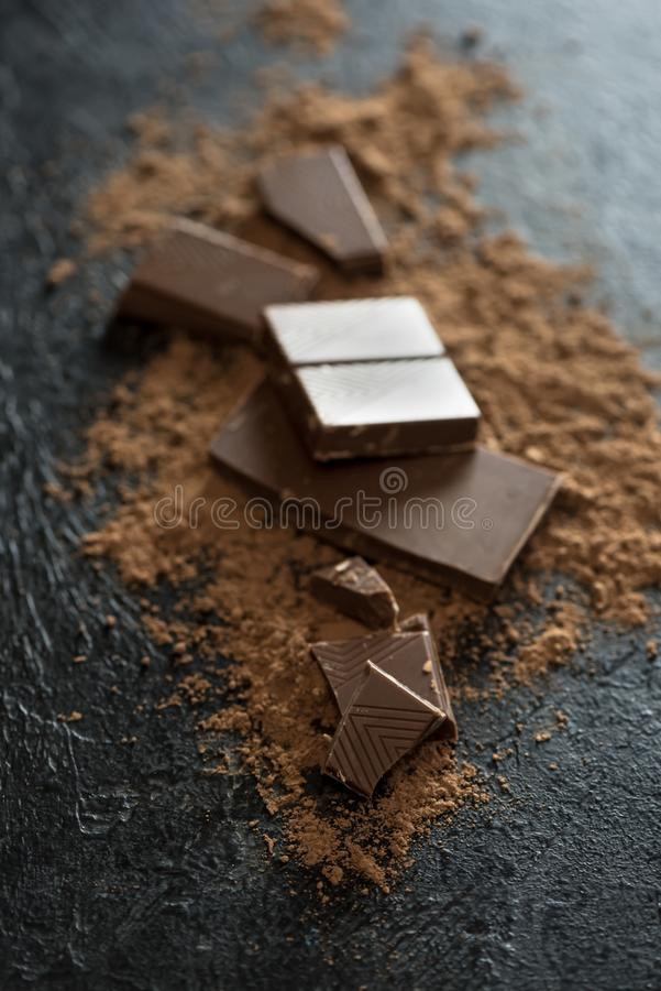 Chocolate pieces and cocoa powder. Broken chocolate pieces and cocoa powder on black. Chunks of chocolate onr dark stone background stock photography