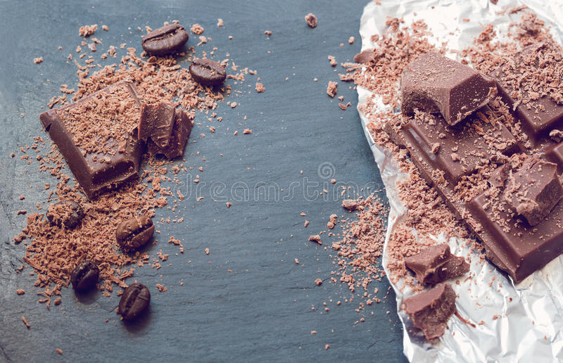 Broken chocolate pieces and cocoa powder on Stone background and foil. Retro royalty free stock images
