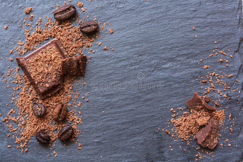 Broken chocolate pieces and grated chocolate on Stone background. Copy-spase. Broken chocolate pieces and grated chocolate on Stone background, Copy-spase stock image