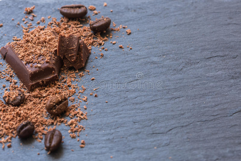 Broken chocolate pieces and grated chocolate on Stone background. Copy-spase. Broken chocolate pieces and grated chocolate on Stone background, Copy-spase royalty free stock image