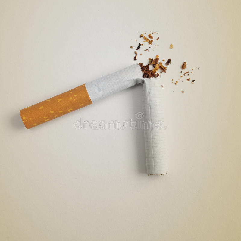 A broken cigarette on a beige background. Symbolizing quitting smoking royalty free stock image