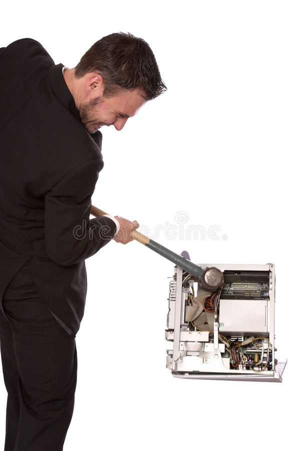Broken computer 2. Young businessman destroying a computer with a sledge hammer stock image