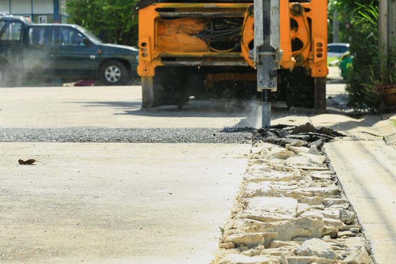 Broken concrete road after machine drilled. With Excavator Breaking Concrete drilling the road blurred background stock images