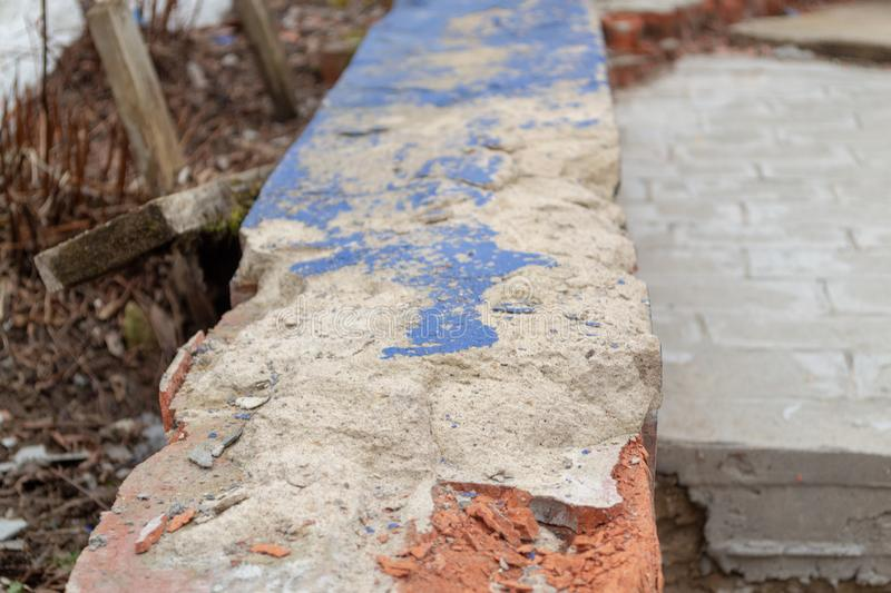 Broken concrete surface on the bricks with the blue paint coming off. Peeling blue paint royalty free stock images