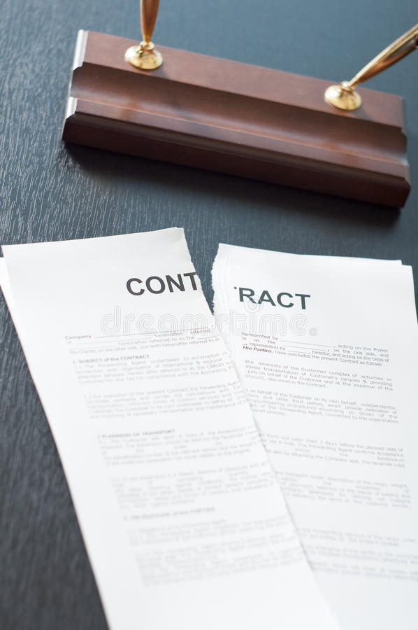 Broken Contract. Terminate the contract on a black table with a pen royalty free stock photography