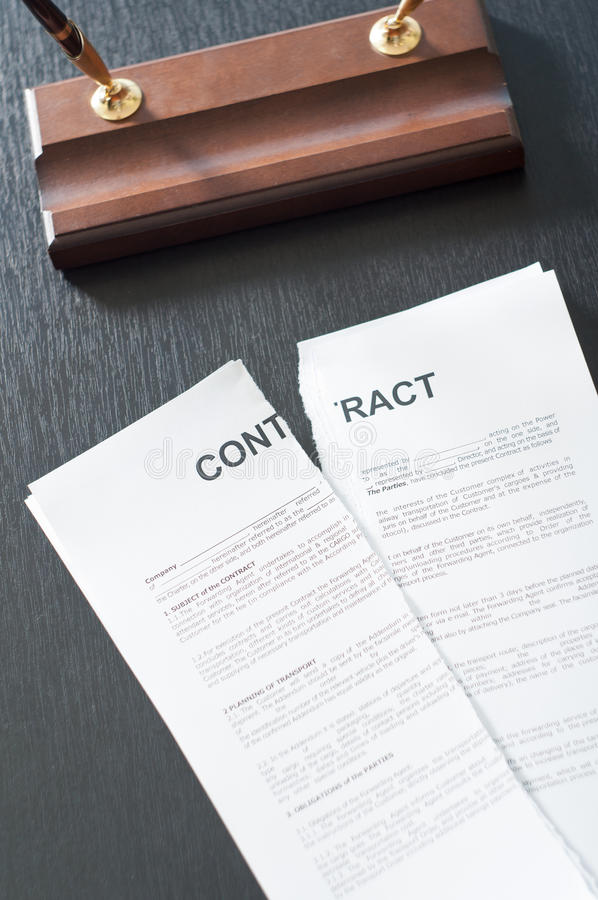 Broken Contract. Terminate the contract on a black table with a pen royalty free stock image