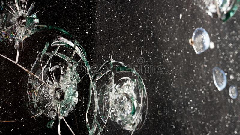 broken cracked glass with hole over black background stock photos