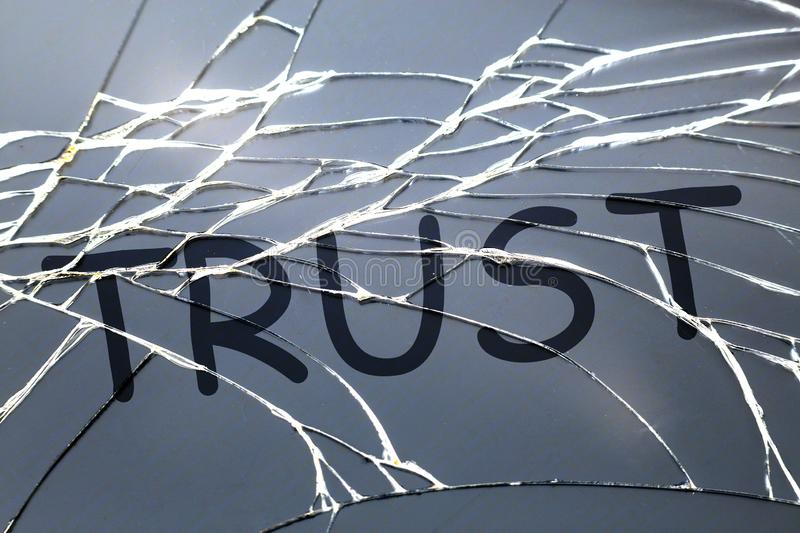 Broken cracked glass with word. `Trust` on it royalty free stock images