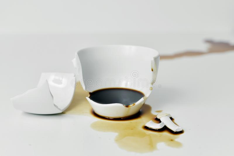 Broken cup of coffee. A broken white ceramic cup of coffee with its pieces and the coffee spilled on a white table royalty free stock images