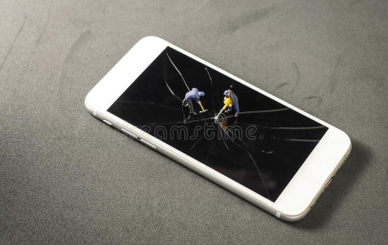 Broken damage screen of mobile phone. Two miniature worker drilling to the broken damage screen of mobile phone stock photos