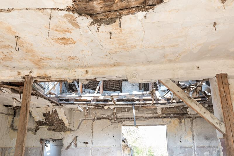 Broken damaged and collapsed ceiling and roof of old house abandoned after aftermath disaster and heavy rain leakage.  stock photo