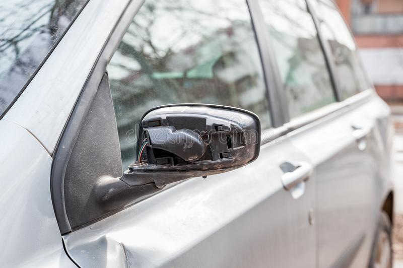 Broken and damaged side mirror on the car doors with remaining wires holding plastic frame without glass. Damaged car, Broken and damaged side mirror on the car stock photo