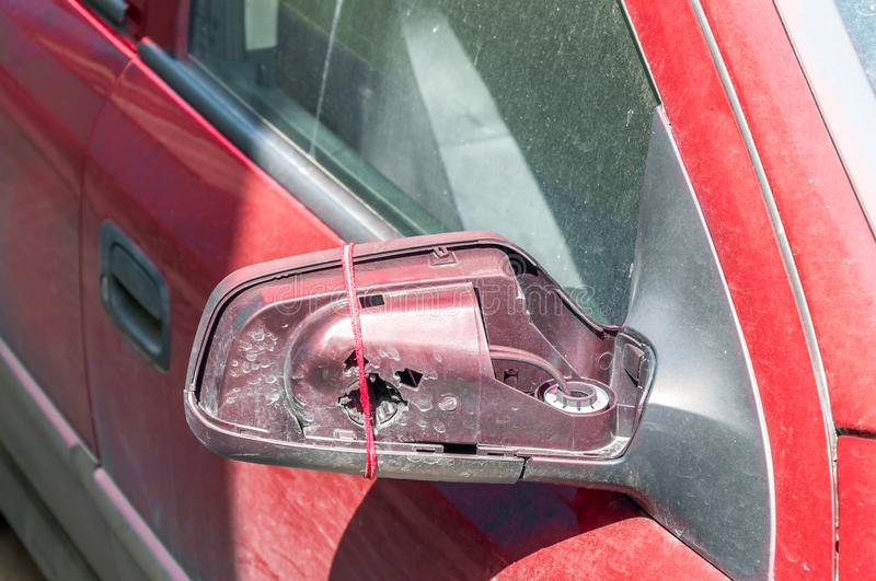 Broken and damaged side mirror plastic cover on the red car doors tied with rope to hold the glass royalty free stock photo