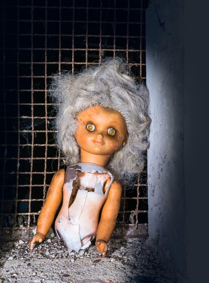 Broken deserted doll lit by mystery light royalty free stock image