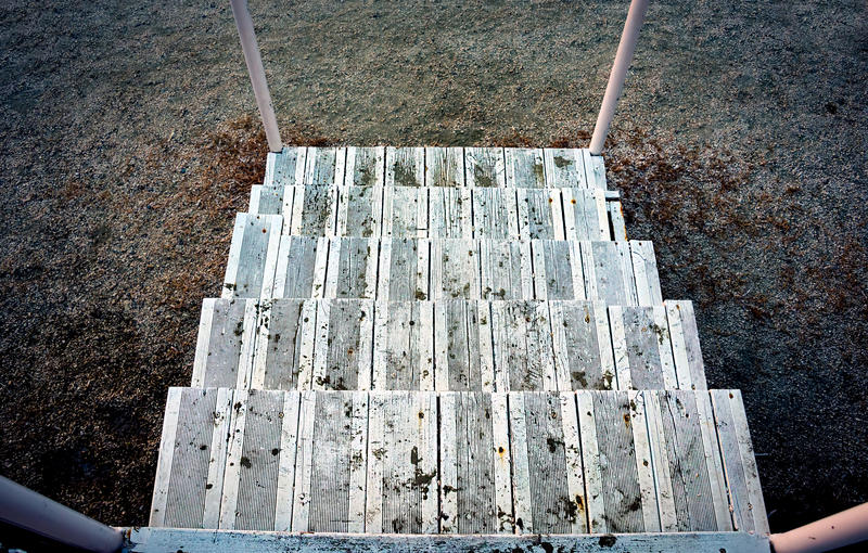 Broken deserted wooden stairs pointing down to the ground stock photos