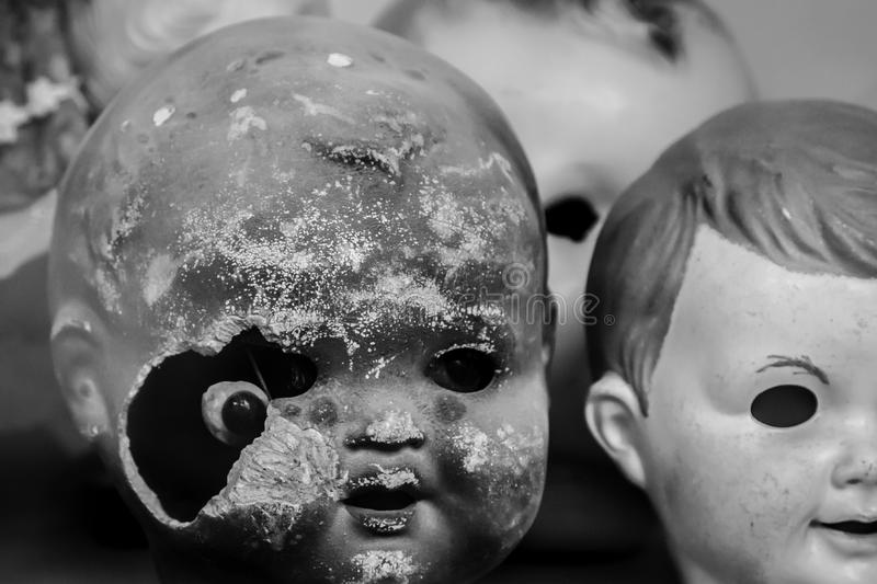 Broken and destroyed face of a doll in black and white. View of old doll parts showing a destroyed broken and burned face of a doll stock photos