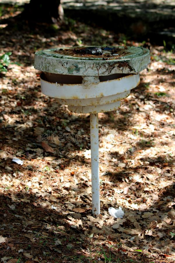 Broken and destroyed rusted small street lamp in shade of trees next to forest path surrounded with dry fallen leaves and trees stock images