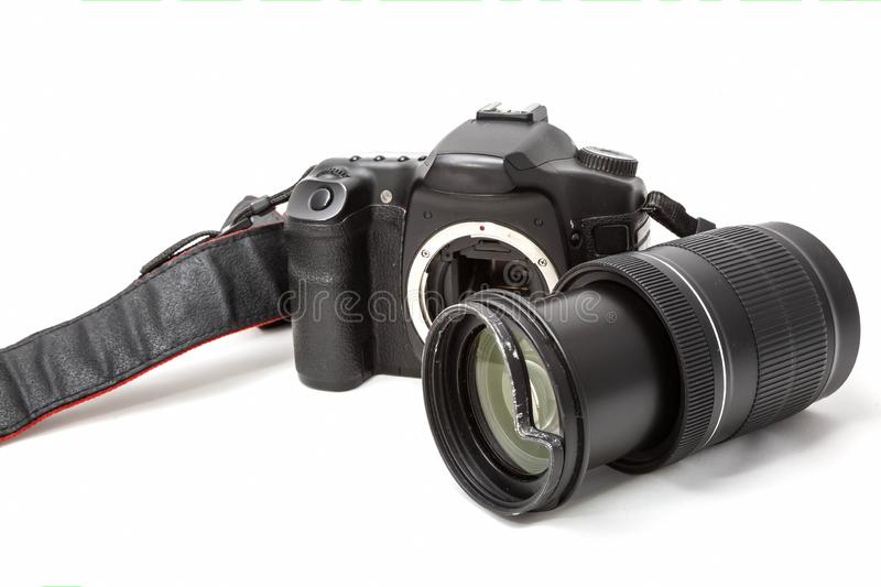 Broken digital SLR camera, dented protective filter on the zoom lens. Will be repaired. Isolated on white background. Side view royalty free stock image