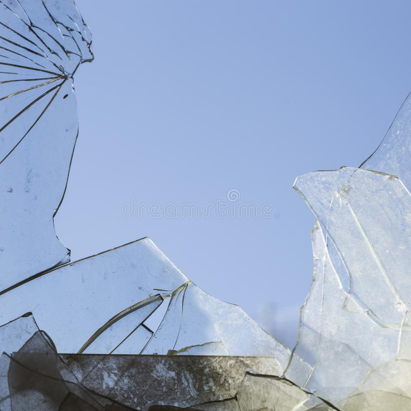Broken dirty glass in blue background stock photos