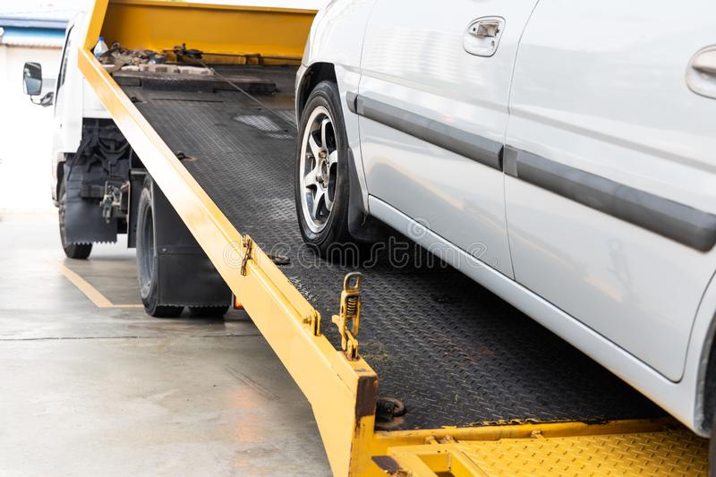 Broken down car towed onto flatbed tow truck with hook cable stock images