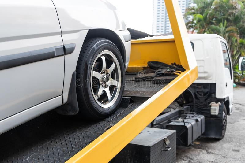 Broken down car towed onto flatbed tow truck with hook cable stock photo