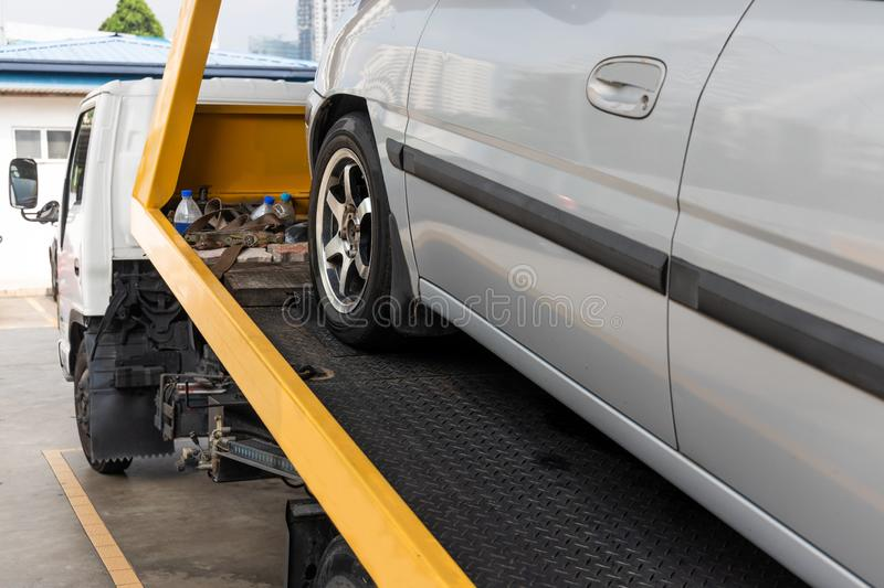 Broken down car towed onto flatbed tow truck with hook cable stock photography