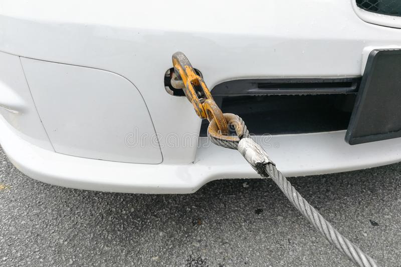Broken down car fitted with hook and chain being towed. By tow truck royalty free stock images