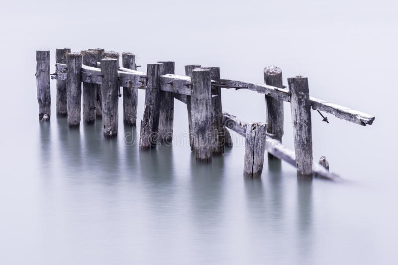 Broken down old pier posts in calm water, covered with light dusting of snow royalty free stock photo
