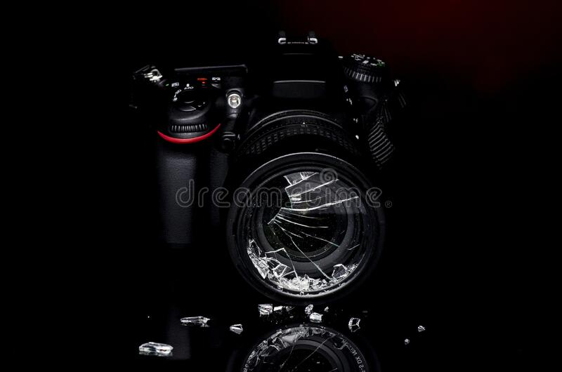 Broken DSLR photo camera filter with reflection. DSLR camera after suffering accident showing glass pieces off the protection filter stock photos