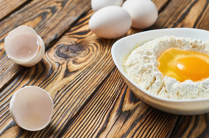 Broken egg in ceramic bowl with flour lies near shells on rustic wooden table stock photos