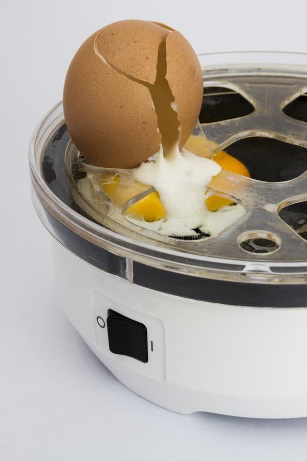 Broken egg in cooker stock images