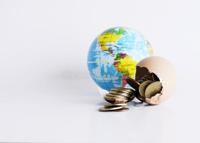 Broken egg with money coins and earth ball for Finance concept. Close up of Broken egg with money coins and earth ball for Finance concept royalty free stock image
