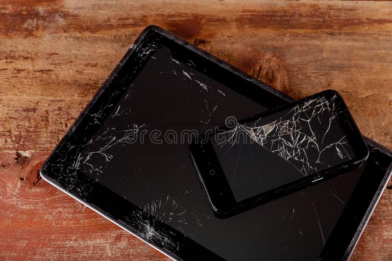 Broken electronic device on wooden background touch screen. Broken tablet and smart phone touch screen electronic device on wooden background accident crack stock photos
