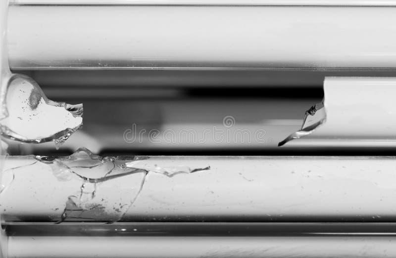 Broken energy saving bulb, compact fluorescent lamp tubular type. Shattered glass tubes. Broken energy saving bulb, compact fluorescent lamp tubular type stock photo