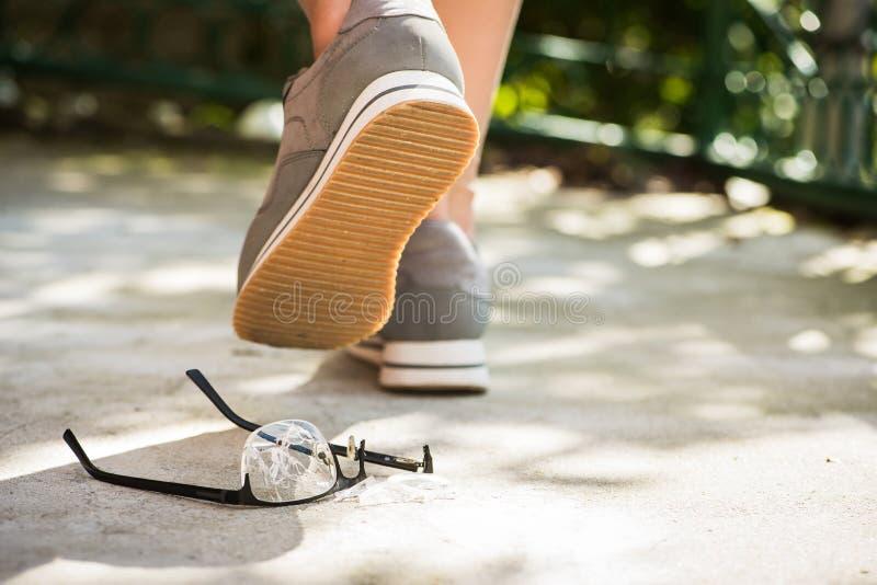 broken eyeglasses on asphalt stock photo