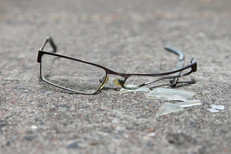 Broken eyeglasses on concrete royalty free stock photography
