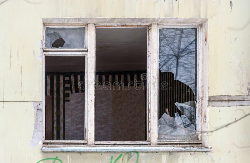 broken fönster Övergiven boningshus i Ryssland arkivbilder