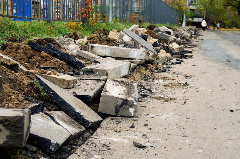 Broken freshly dug up old curbstones with pieces of an asphalt and earth lying on the road in Moscow. stock photography