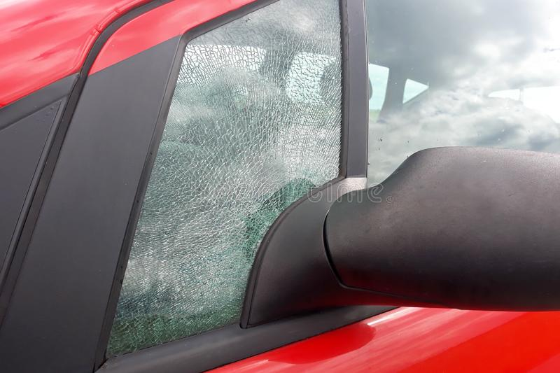 Broken front side car glass fractured into countless  small pieces royalty free stock images