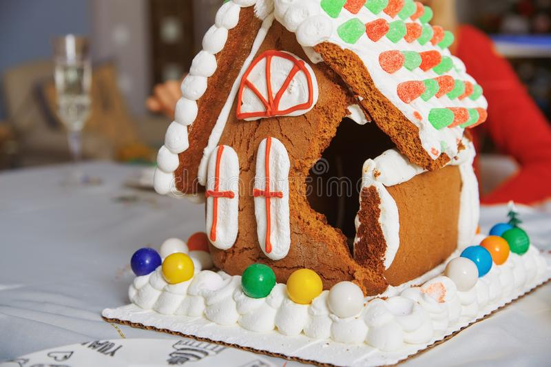 Broken Gingerbread house on the table in Christmas decorated room stock photo