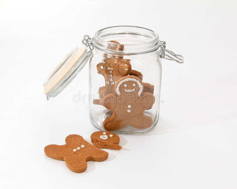Broken gingerbread man. Gingerbread man broken outside a glass cookie jar royalty free stock photos