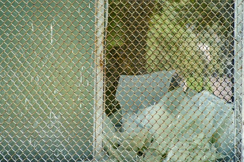 Broken glass behind the grid royalty free stock image