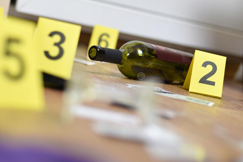 Broken glass and bottle of wine marked as evidence during crime scene investigation. Many yellow markers with numbers stock images