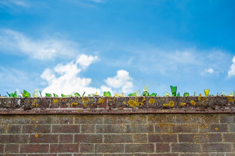 Broken glass bottles cemented to the top of a brick wall. Broken glass bottles cemented to the top of a brick wall, helping to create a deterrent from people royalty free stock image