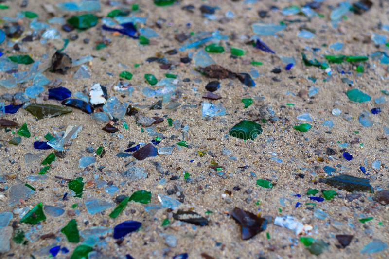 Broken glass bottles on white sand. Bottles is green and blue colour. Trash on the sand. Ecological problem royalty free stock photo