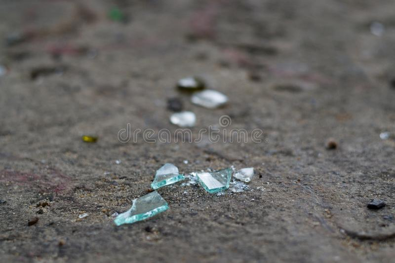Broken glass bottles on white sand. Trash on the sand. Ecological problem royalty free stock images