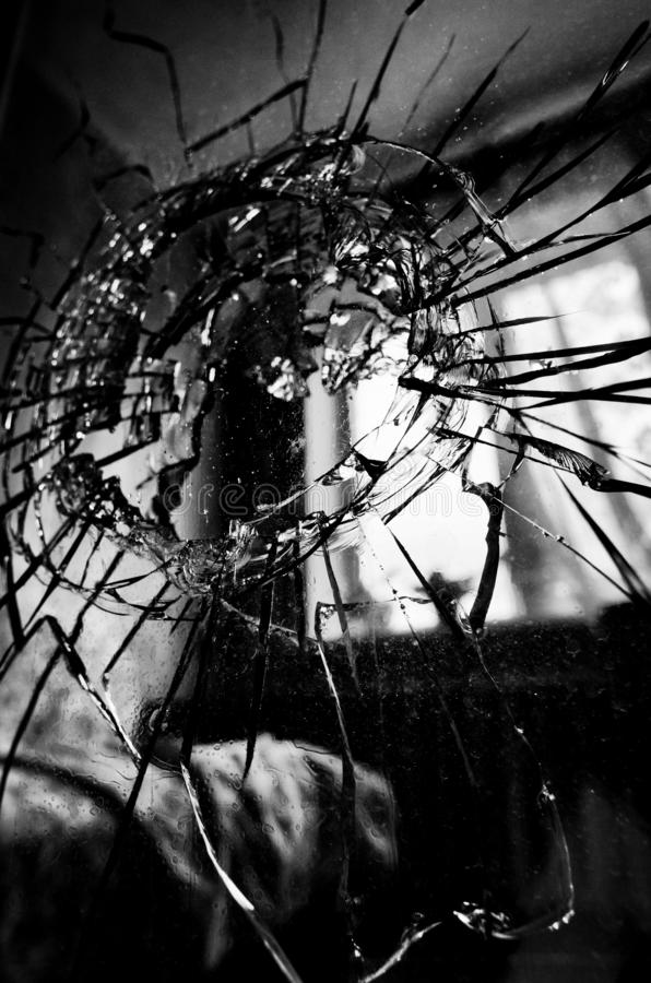 Broken glass with cracks and a hole closeup royalty free stock images