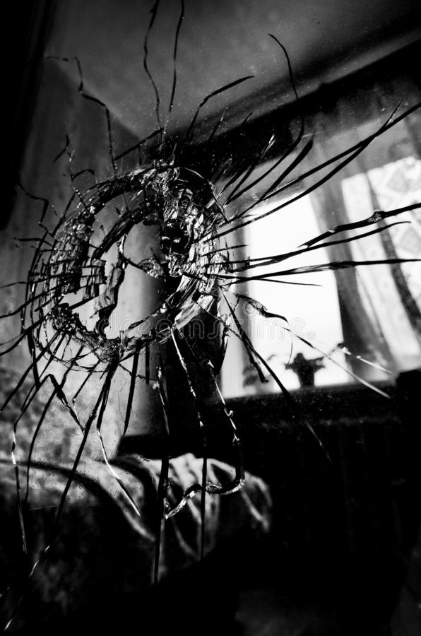 Broken glass with cracks and a hole stylized black and white film royalty free stock images
