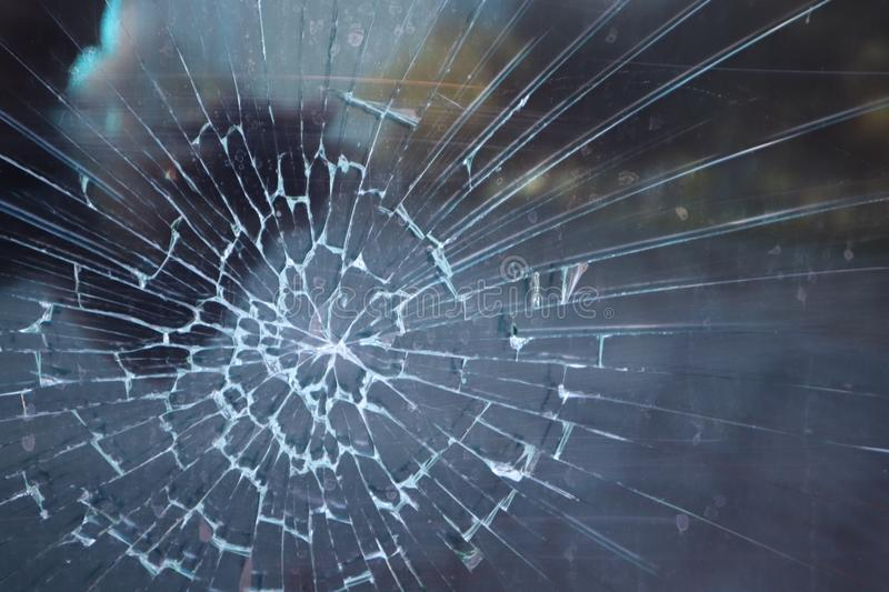 Broken glass. Criminal incident at the bus stop. Hole and cracks in the glass of a city bus stop. Cracked glass Texture. Cracked g royalty free stock photos